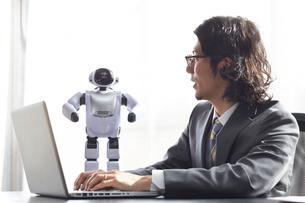 パソコンをしながらロボットと話す男性の写真素材 [FYI01468677]