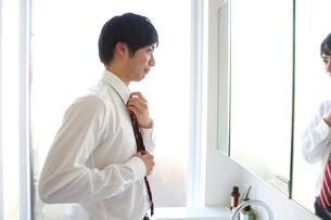 鏡の前で身支度をする若いビジネスマンの写真素材 [FYI01468679]