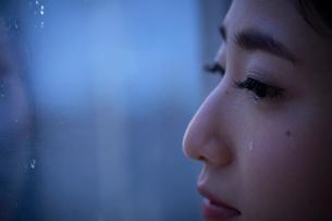 窓際で涙を流す女性のアップの写真素材 [FYI01468681]