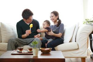 ソファでくつろぐ若い3人家族の写真素材 [FYI01468687]