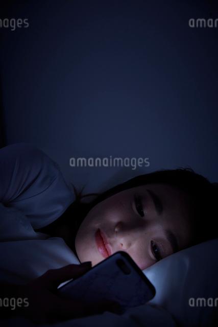 暗闇の中ベットに寝転んでスマートフォンを見る女性の写真素材 [FYI01468688]
