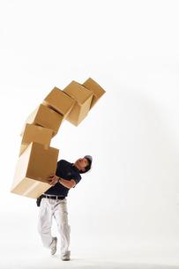 白バックの空間でたくさん重なったダンボールを運ぶ作業着の男性の写真素材 [FYI01468719]