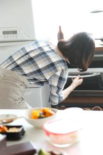 お弁当つくり中に電子レンジをセットする後姿のミドル女性の写真素材 [FYI01468738]