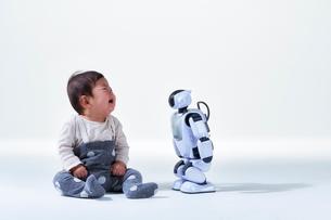 赤ちゃんと向き合うロボットの写真素材 [FYI01468751]