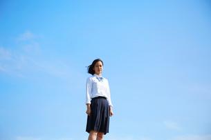 青空の下でカメラの方を見つめる女子高生の写真素材 [FYI01468766]