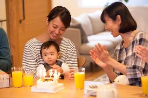 テーブルで赤ちゃんを祝う家族の写真素材 [FYI01468785]