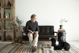 ソファで愛犬と過ごすシニア男性の写真素材 [FYI01468788]