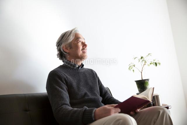 ソファで読書するぐシニア男性の写真素材 [FYI01468790]