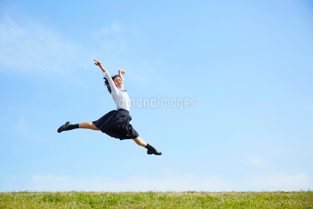 河川敷でジャンプする女子高生の写真素材 [FYI01468802]