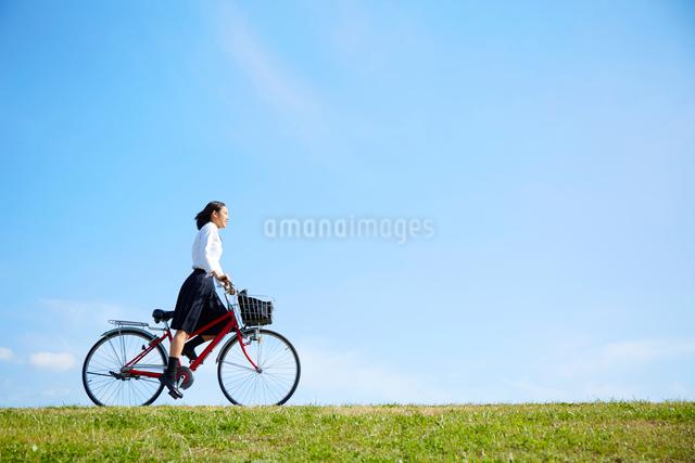 河川敷を自転車で走る女子高生の写真素材 [FYI01468808]