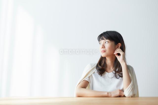 頬杖を付いて窓の外を見る女性の写真素材 [FYI01468843]