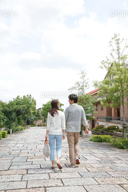 新緑の住宅街を歩く後姿の若いカップルの写真素材 [FYI01468874]