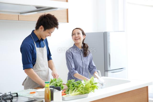 キッチンで微笑む若いカップルの写真素材 [FYI01468879]
