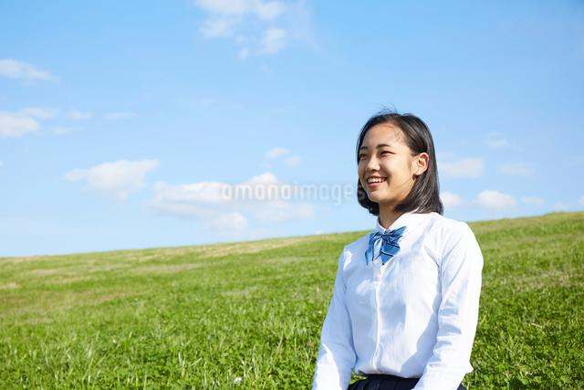 芝生に座る笑顔の女子高生の写真素材 [FYI01468889]