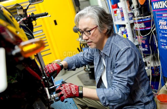 バイクを修理するシニア男性の写真素材 [FYI01468898]