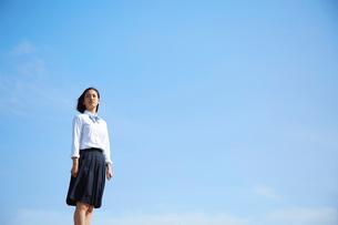 青空の下で遠くを見つめる女子高生の写真素材 [FYI01468910]