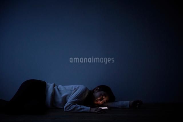 暗い部屋でスマートフォンを見て床に倒れこむ女性の写真素材 [FYI01468942]