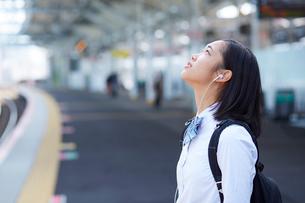 駅のホームでイヤホンで音楽を聴く女子高生の写真素材 [FYI01468950]