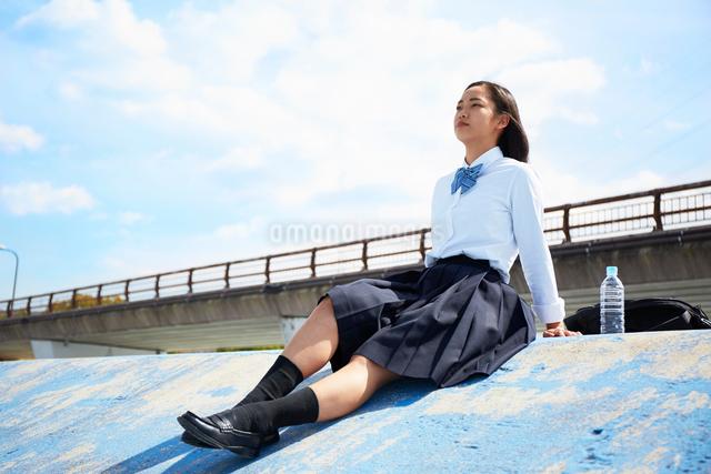 土手で足を伸ばして座る女子高生の写真素材 [FYI01468958]