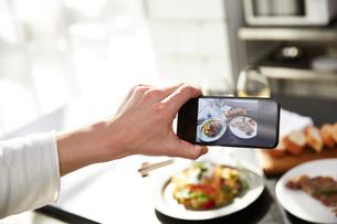 料理を携帯のカメラで撮る男性の写真素材 [FYI01468964]