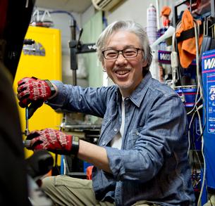 バイクを修理するシニア男性の写真素材 [FYI01468965]