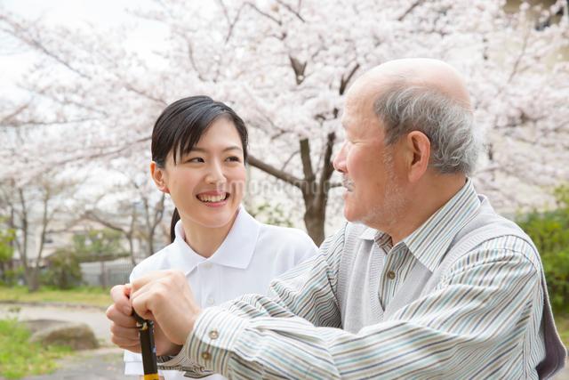 座りながら談笑するシニア男性と介護福祉士の写真素材 [FYI01468997]