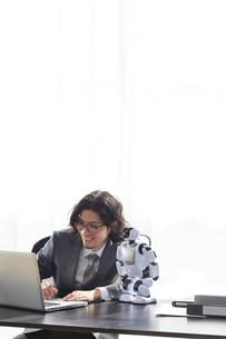 ロボットとパソコンを見るスーツを着た男性の写真素材 [FYI01469053]