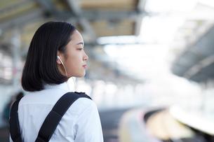 駅のホームでイヤホンで音楽を聴く女子高生の写真素材 [FYI01469063]