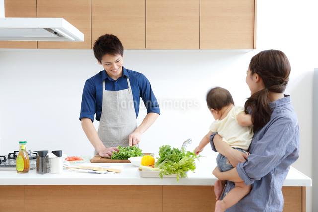 キッチンで料理する若い男性との赤ちゃんを抱く若い女性の写真素材 [FYI01469084]