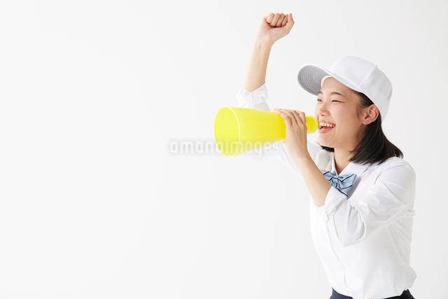 メガホンを持って叫ぶ帽子をかぶった女子高生の写真素材 [FYI01469113]