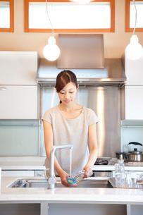 キッチンで洗い物をする若い女性の写真素材 [FYI01469119]