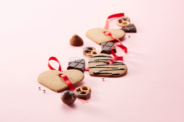 ピンクの背景に並んだクッキーとチョコレートの写真素材 [FYI01469121]