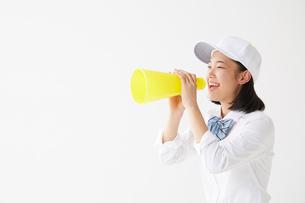 メガホンを持って叫ぶ帽子をかぶった女子高生の写真素材 [FYI01469122]