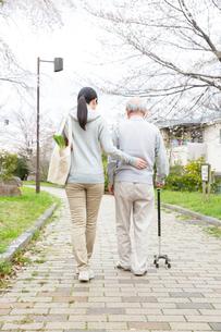杖のシニア男性と歩く買い物袋を提げた後姿の女性ヘルパーの写真素材 [FYI01469135]