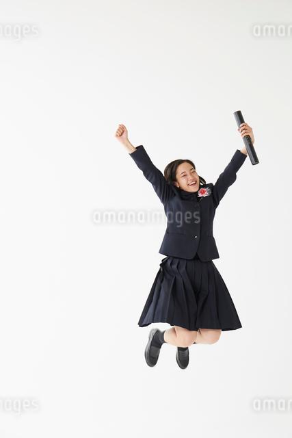 卒業証書の筒を持ってジャンプする女子高生の写真素材 [FYI01469138]