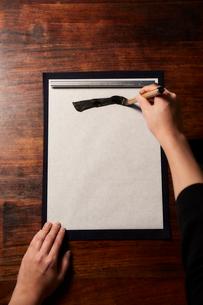机で書道をする女性の手の写真素材 [FYI01469200]