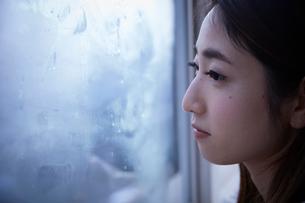 窓際で暗い表情をして外を見る女性の写真素材 [FYI01469423]