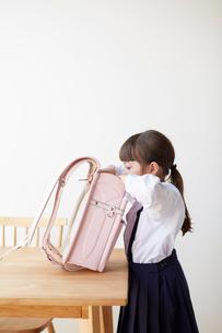 テーブルでランドセルを探る女の子の写真素材 [FYI01469429]