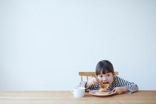テーブルでホットケーキを食べる女の子の写真素材 [FYI01469480]