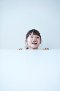 白いテーブルの下から覗く女の子の写真素材 [FYI01469506]