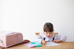 テーブルでランドセルを広げて勉強する女の子の写真素材 [FYI01469589]