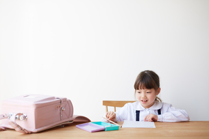 テーブルでランドセルを広げて勉強する女の子の写真素材 [FYI01469591]