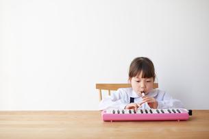 テーブルで鍵盤ハーモニカをする女の子の写真素材 [FYI01469594]