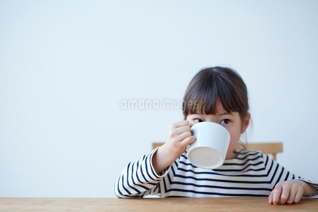 テーブルで大きいマグカップでジュースをのむ女の子の写真素材 [FYI01469595]