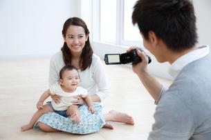 動画を撮る若い3人家族の写真素材 [FYI01469602]