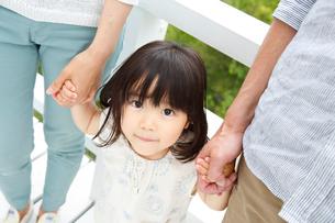 両親に手を繋がれてはにかむ女の子の写真素材 [FYI01469640]