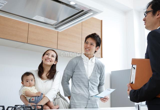 モデルキッチンで説明を受ける赤ちゃん連れの若い3人家族の写真素材 [FYI01469654]