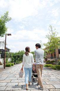新緑の住宅街でベビーカーを押す後姿の若いカップルの写真素材 [FYI01469709]