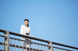 陸橋に立って景色を眺める女性の写真素材 [FYI01469743]