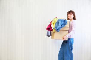 段ボール箱に入った服を運ぶ女性の写真素材 [FYI01469819]